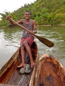 Rowing across the river in the dugout canoe with our friend from the village.